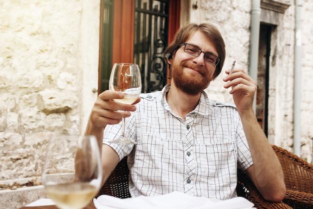 Uomo bello con bicchiere di vino in street cafe