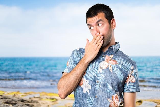 Uomo bello con camicia di fiori che copre la sua bocca in spiaggia