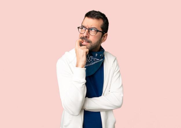 Uomo bello con gli occhiali avendo dubbi mentre alzando lo sguardo su sfondo rosa isolato