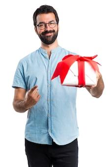 Uomo bello con gli occhiali blu che detengono un regalo