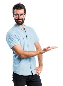 Uomo bello con gli occhiali blu che presentano qualcosa