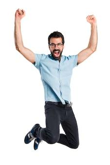 Uomo bello con gli occhiali blu che salta