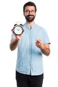Uomo bello con gli occhiali blu che tiene orologio