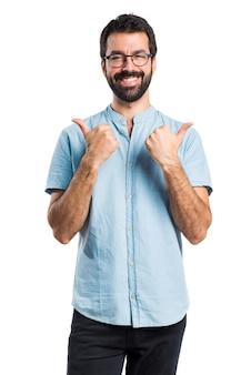 Uomo bello con gli occhiali blu con il pollice in su