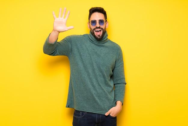 Uomo bello con gli occhiali da sole che saluta con la mano con l'espressione felice