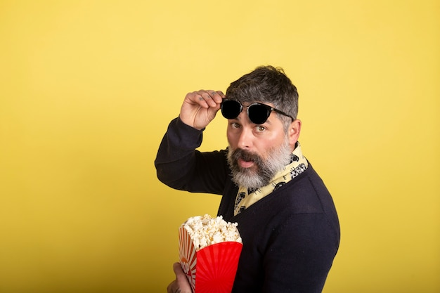 Uomo bello con gli occhiali da sole nel profilo che esamina macchina fotografica che giudica una scatola piena di popcorn su fondo giallo.