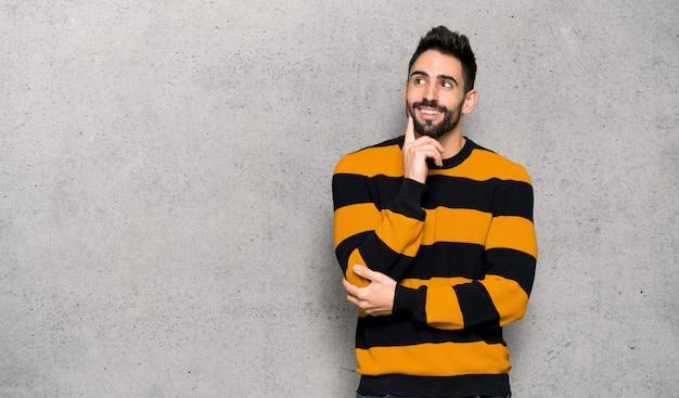 Uomo bello con il maglione a strisce che pensa un'idea mentre cerca sopra la parete strutturata