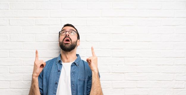Uomo bello con il muro di mattoni bianco della barba sorpreso e rivolto verso l'alto