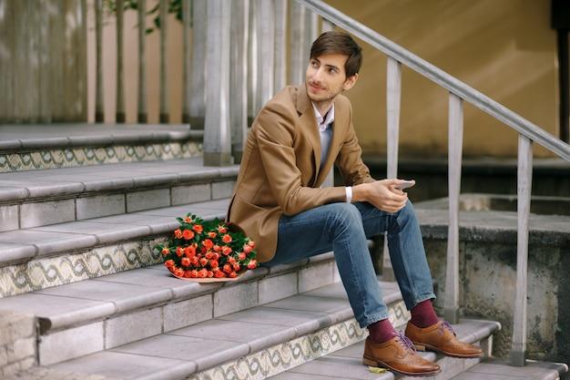 Uomo bello con il telefono e il mazzo di rose