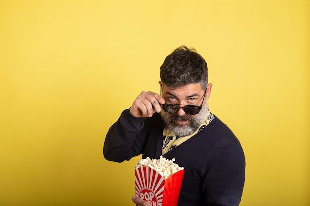 Uomo bello con la barba bianca e gli occhiali da sole che esaminano macchina fotografica che giudica una scatola piena di popcorn su fondo giallo.