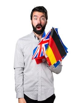 Uomo bello con la barba che detiene molte bandiere e facendo gesto di sorpresa