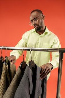 Uomo bello con la barba che sceglie la camicia in un negozio