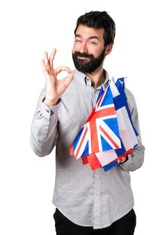 Uomo bello con la barba che tiene molte bandiere e che fa il segno di ok