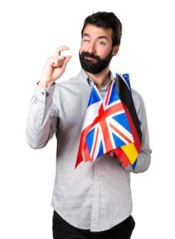 Uomo bello con la barba che tiene molte bandiere e che fa piccolo segno