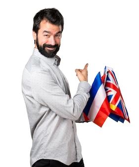 Uomo bello con la barba che tiene molte bandiere e che indica indietro