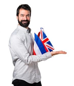 Uomo bello con la barba che tiene molte bandiere e presenta qualcosa