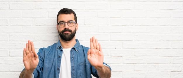 Uomo bello con la barba sopra il muro di mattoni bianchi che fa gesto di arresto e deludente