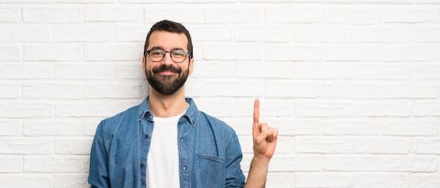 Uomo bello con la barba sopra il muro di mattoni bianchi che mostra e che solleva un dito nel segno del meglio