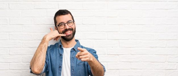 Uomo bello con la barba sopra il muro di mattoni bianco che fa gesto del telefono e che indica parte anteriore