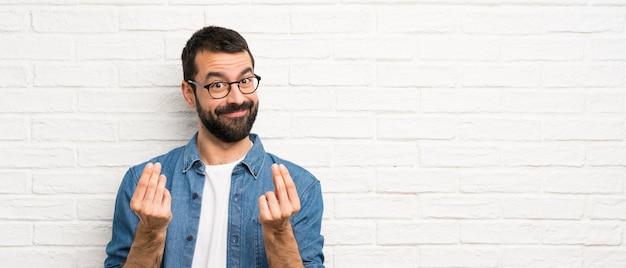 Uomo bello con la barba sopra il muro di mattoni bianco che fa gesto di soldi