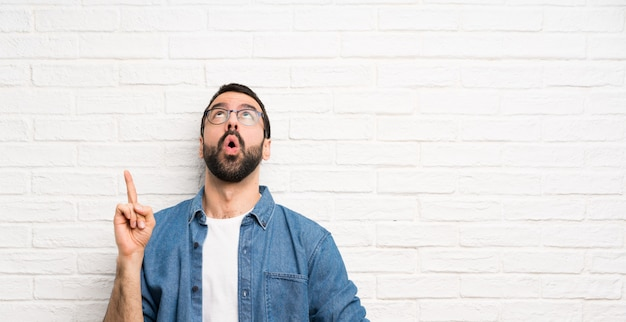 Uomo bello con la barba sopra il muro di mattoni bianco che indica su e sorpreso