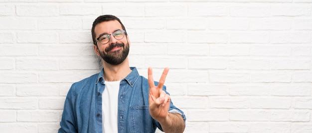 Uomo bello con la barba sopra il muro di mattoni bianco che sorride e che mostra il segno di vittoria