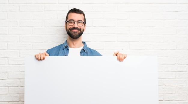 Uomo bello con la barba sopra il muro di mattoni bianco che tiene un cartello vuoto