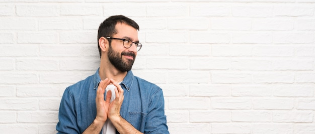 Uomo bello con la barba sopra il muro di mattoni bianco che traccia qualcosa
