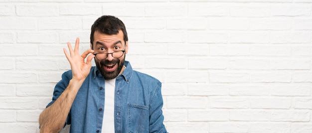 Uomo bello con la barba sopra il muro di mattoni bianco con gli occhiali e sorpreso