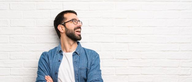Uomo bello con la barba sopra il muro di mattoni bianco felice e sorridente