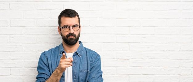 Uomo bello con la barba sopra il muro di mattoni bianco frustrato e indicando la parte anteriore