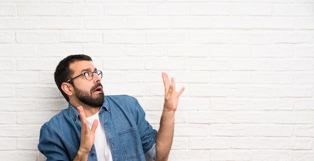 Uomo bello con la barba sopra il muro di mattoni bianco nervoso e spaventato