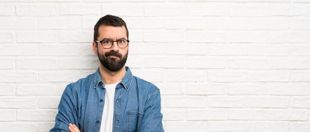 Uomo bello con la barba sopra la sensibilità bianca del muro di mattoni turbato