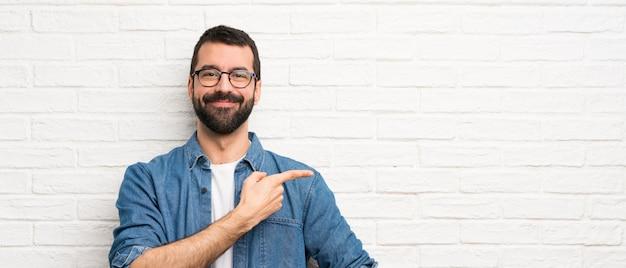 Uomo bello con la barba sul muro di mattoni bianchi che punta il dito verso il lato