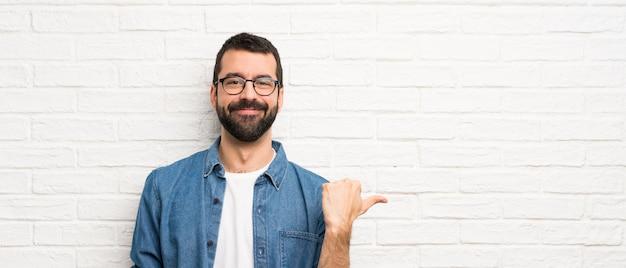 Uomo bello con la barba sul muro di mattoni bianchi che punta verso il lato per presentare un prodotto