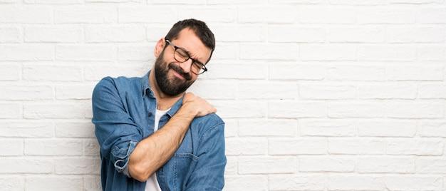 Uomo bello con la barba sul muro di mattoni bianchi che soffrono di dolore alla spalla per aver fatto uno sforzo