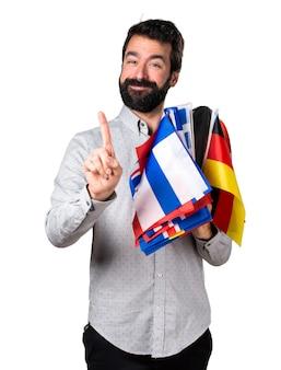 Uomo bello con la barba tenendo molte bandiere e contando uno