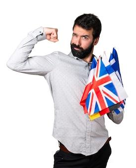 Uomo bello con la barba tenendo molte bandiere e facendo un gesto forte
