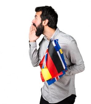 Uomo bello con la barba tenendo molte bandiere e gridando