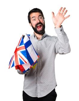 Uomo bello con la barba tenendo molte bandiere e salutando