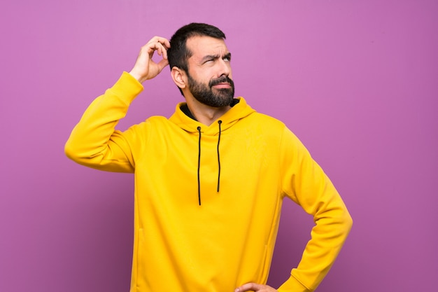 Uomo bello con la felpa gialla che ha dubbi mentre gratta la testa