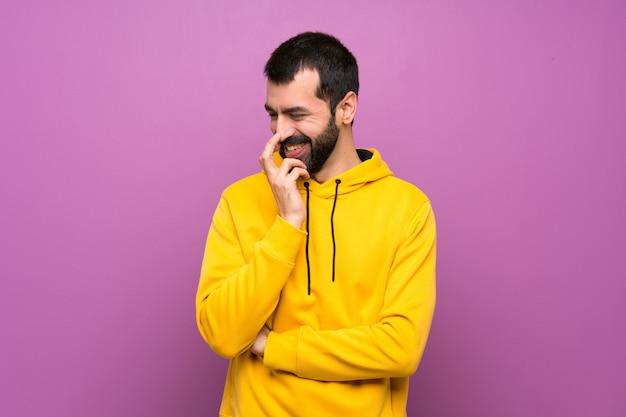 Uomo bello con la felpa gialla che sorride molto