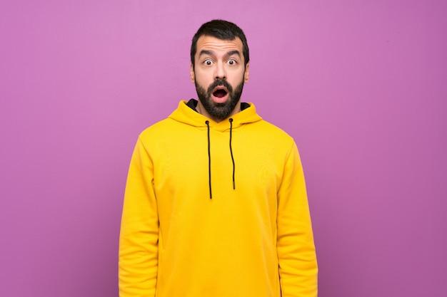 Uomo bello con la felpa gialla con espressione facciale a sorpresa