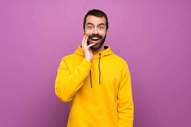 Uomo bello con la felpa gialla con espressione facciale sorpresa e scioccata
