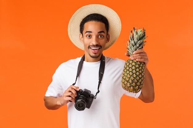 Uomo bello con la maglietta bianca che tiene un ananas