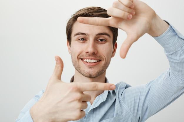 Uomo bello creativo che sorride, mostrando i telai della mano, cattura il momento