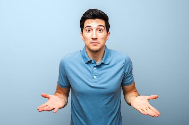 Uomo bello del brunette in camicia di polo blu con il fronte serio che gesturing con le sue mani contro. non c'è niente da fare