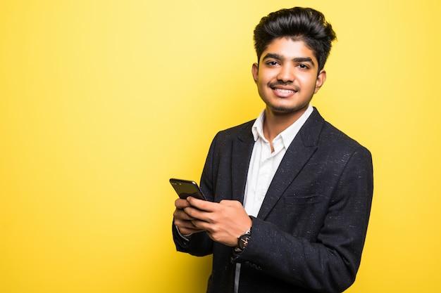 Uomo bello dell'uomo d'affari di asianindian che per mezzo dello smart phone sulla parete gialla