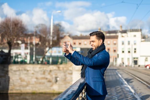 Uomo bello di affari che cattura una maschera con il telefono cellulare all'aperto.