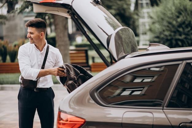 Uomo bello di affari che fa una pausa la sua automobile durante un viaggio d'affari